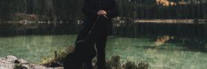 Alex Diehl steht in einer bergigen Landschaft und stützt sich auf seiner Gitarre ab. Er trägt einen Anzug und einen Hut.