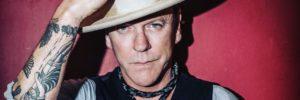 Kiefer Sutherland schaut ernst in die Kamera, trägt einen Hut, den er ganz lässig festhält