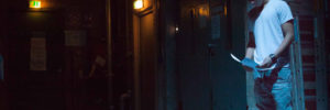 Ein Jugendlicher liest im Stehen in einem dunklen Raum