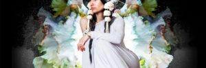 Simrit Kaur sitzt in weißem Kleid vor einer Blüte
