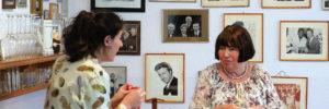 Zwei Frauen unterhalten sich – im Hintergrund hängen Portraits als Bilder in Rahmen