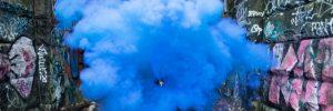 Blauer Rauch in einer Bahnunterführung mit Graffiti an den Wänden