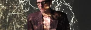 Ein Darsteller vor einer Wand mit Videoprojektion
