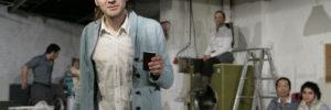 Bildmotiv aus der Inszenierung – im Vordergrund ein Schauspieler mit Kaffeebecher, im HIntergrund eine Waschmaschine und andere Protagonisten