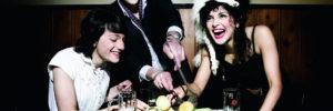 Drei Darsteller um einen Esstisch mit Besteck in den Händen. Einer der drei steht.