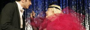 Zwei Schauspieler in Kostüm vor einem glitzernden Vorhang
